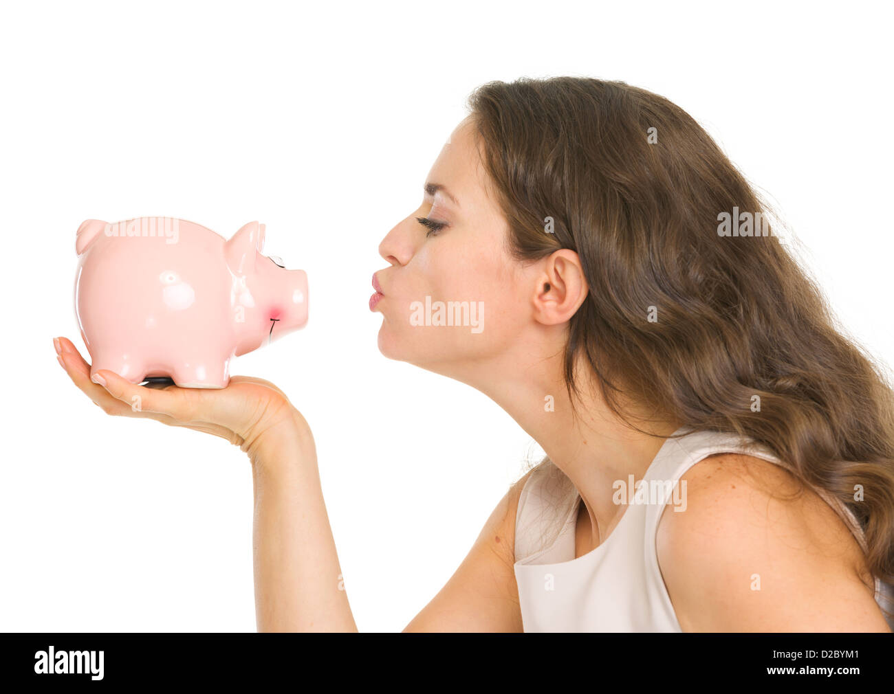 Young woman kissing piggy bank - Stock Image