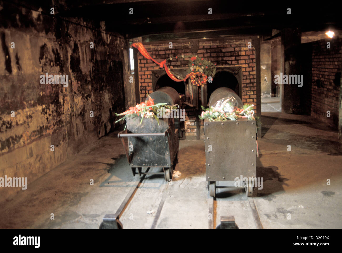 Poland, Auschwitz. Wagons For Loading Corpses Into Crematorium. Ovens In Background. - Stock Image