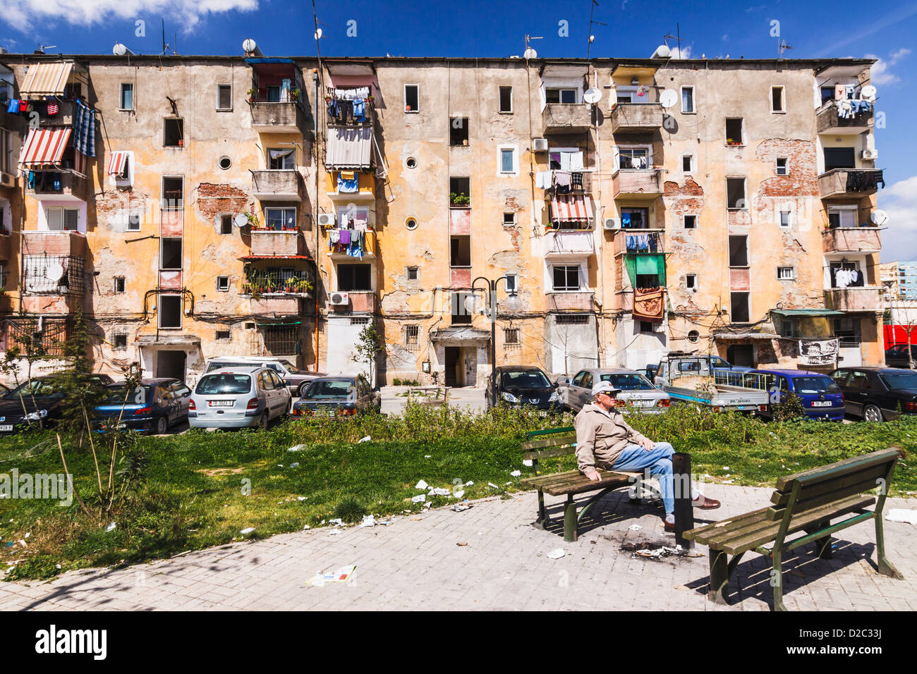 Albanian man sitting on a bench in a rundown park of Tirana, Albania - Stock Image
