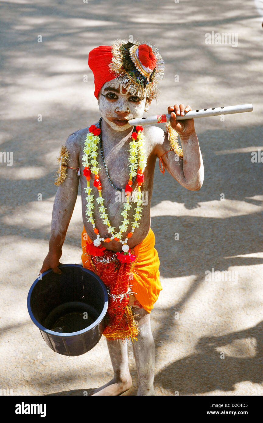 Indian Child Begging, Dressed As Lord Krishna With Flute And Garland - Stock Image