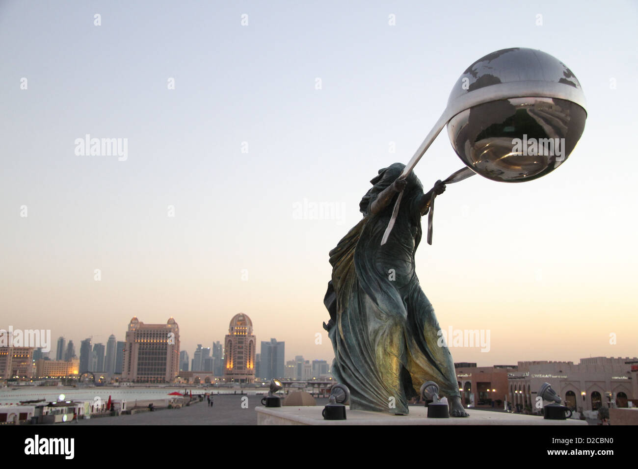 Force of Nature sculpture by Lorenzo Quinn at Katara Cultural Village with the Doha Hilton seen in the background - Stock Image