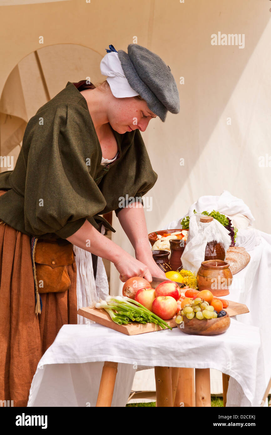 A 17th century woman prepares food - Stock Image
