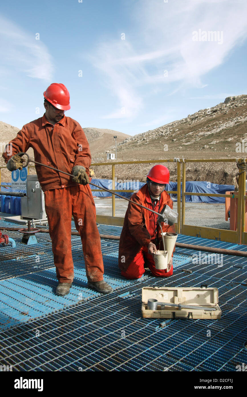 Onshore oil and gas exploration site.Iraqi Kurdish workers taking samples of mud from bore hole before logging in - Stock Image