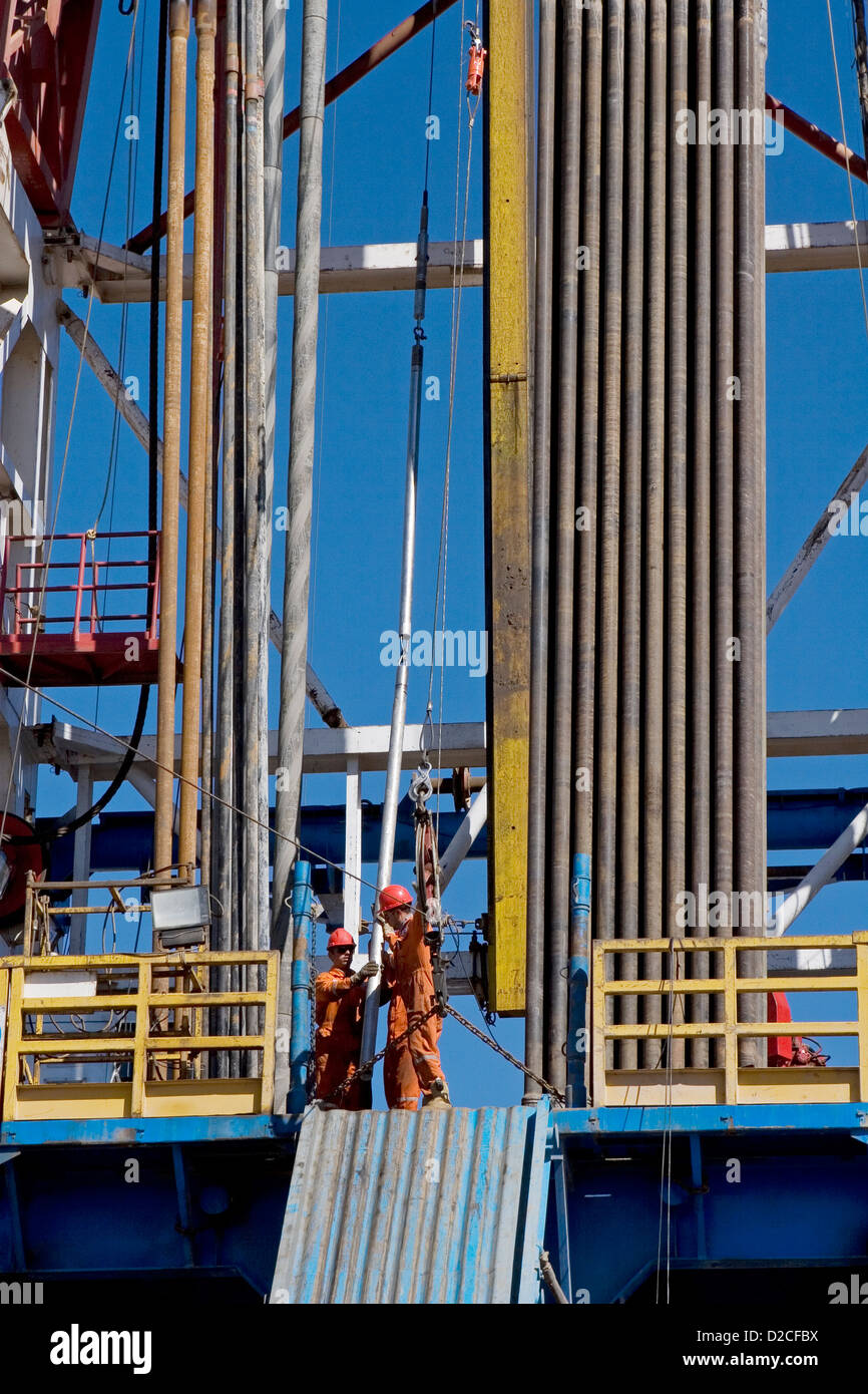 Onshore oil and gas exploration site. Wire line tools being lifted up to rig platform floor before logging. Kurdistan Stock Photo