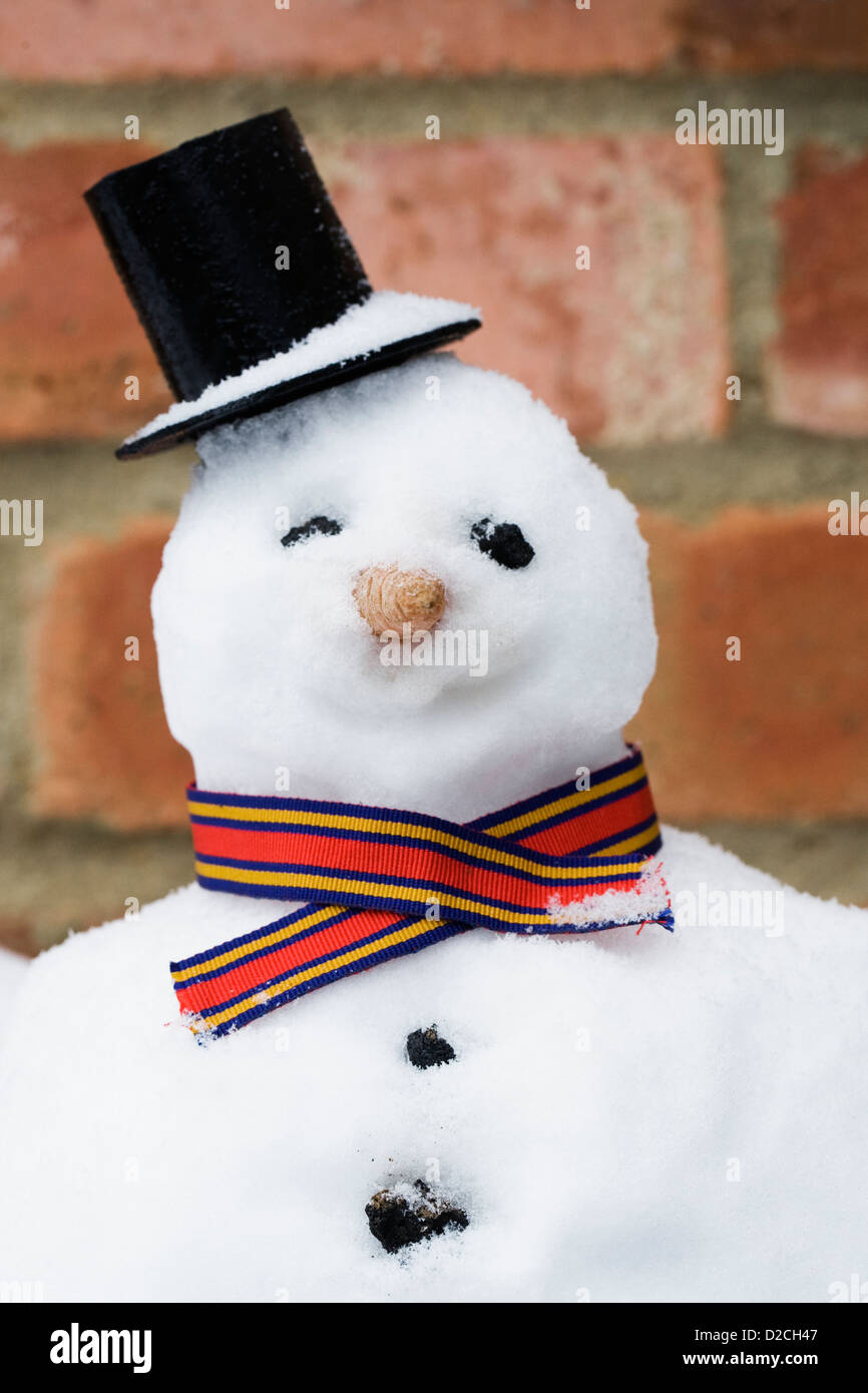 Smiling snowman against a red brick wall. - Stock Image