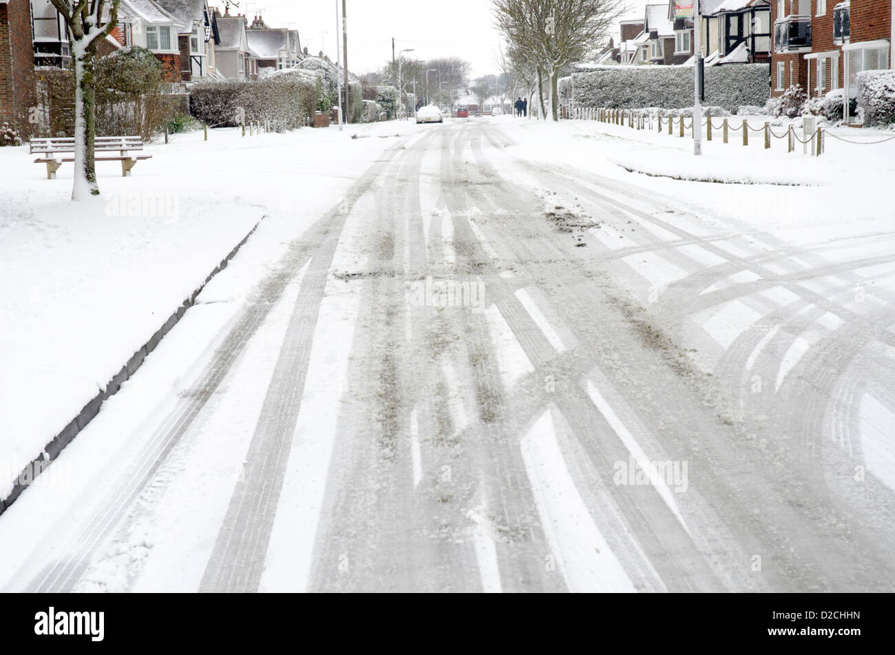 Road covered in snow with tire tracks after a snow fall. - Stock Image