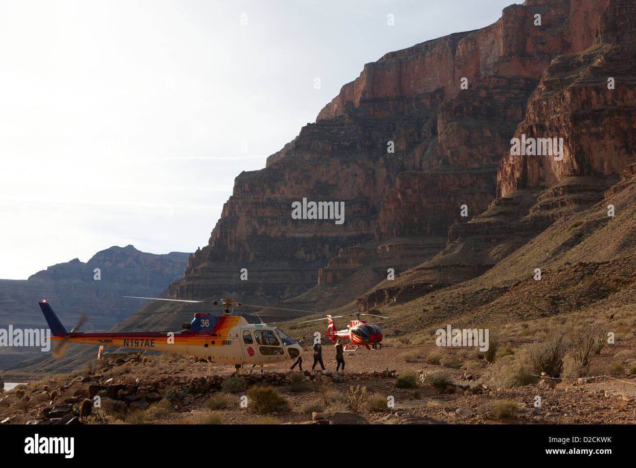 passengers leaving papillon helicopter tours landed on pad down in the Grand canyon Arizona USA - Stock Image