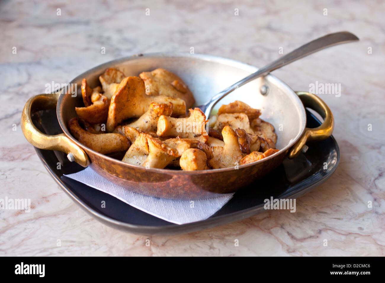 Cooked mushrooms in a copper frying pan. - Stock Image