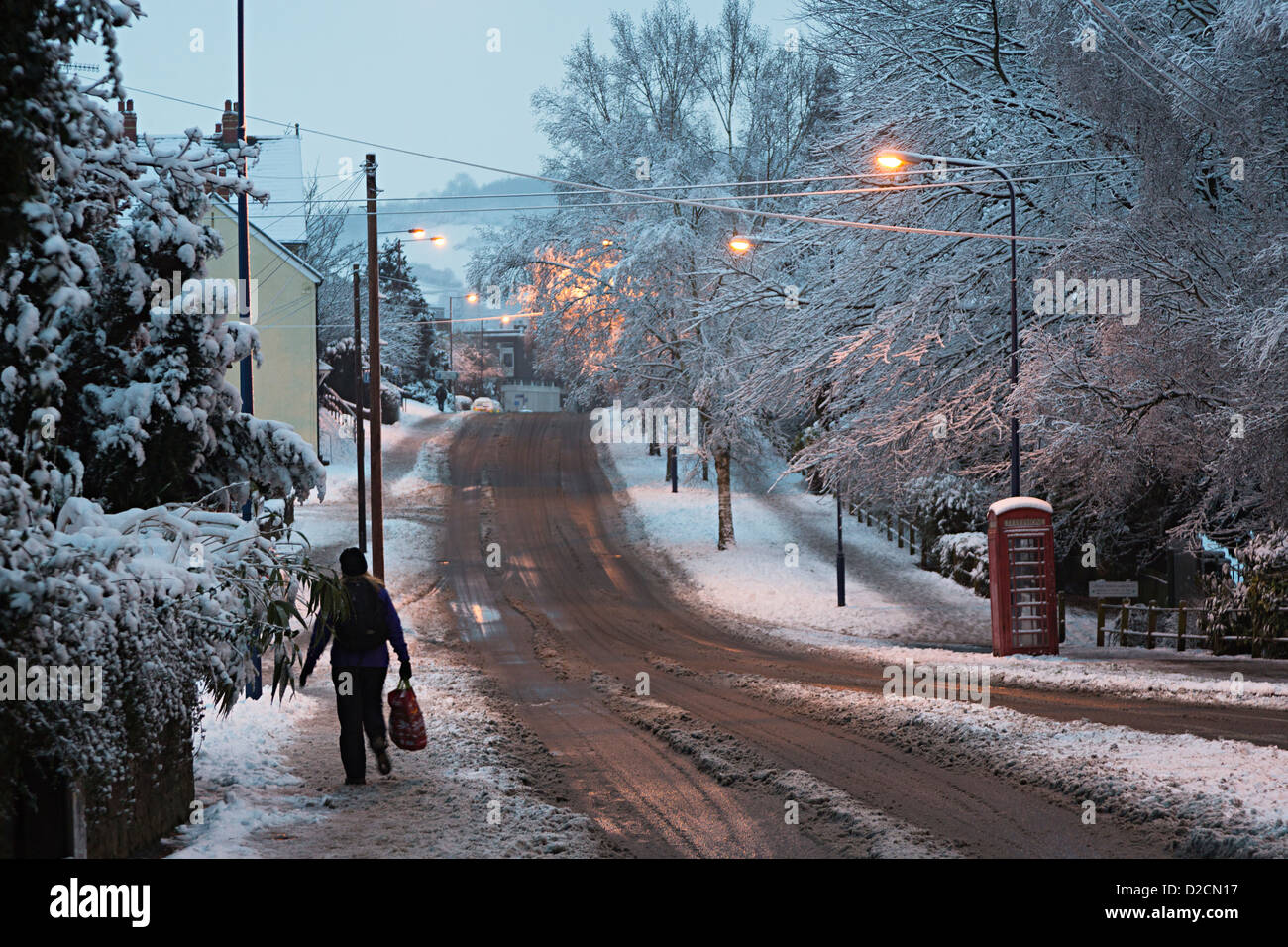 Woman walking with shopping bag on slippery pavement on winter street at dusk, Abergavenny, Wales, UK - Stock Image