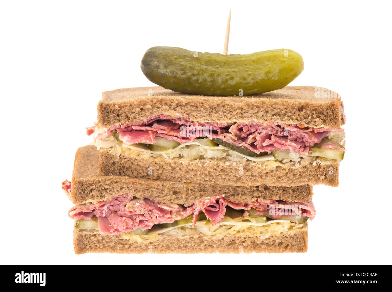 A New York deli pastrami sandwich on rye bread. This sandwich has slices of pastrami, grated Emmental cheese, gherkin, - Stock Image