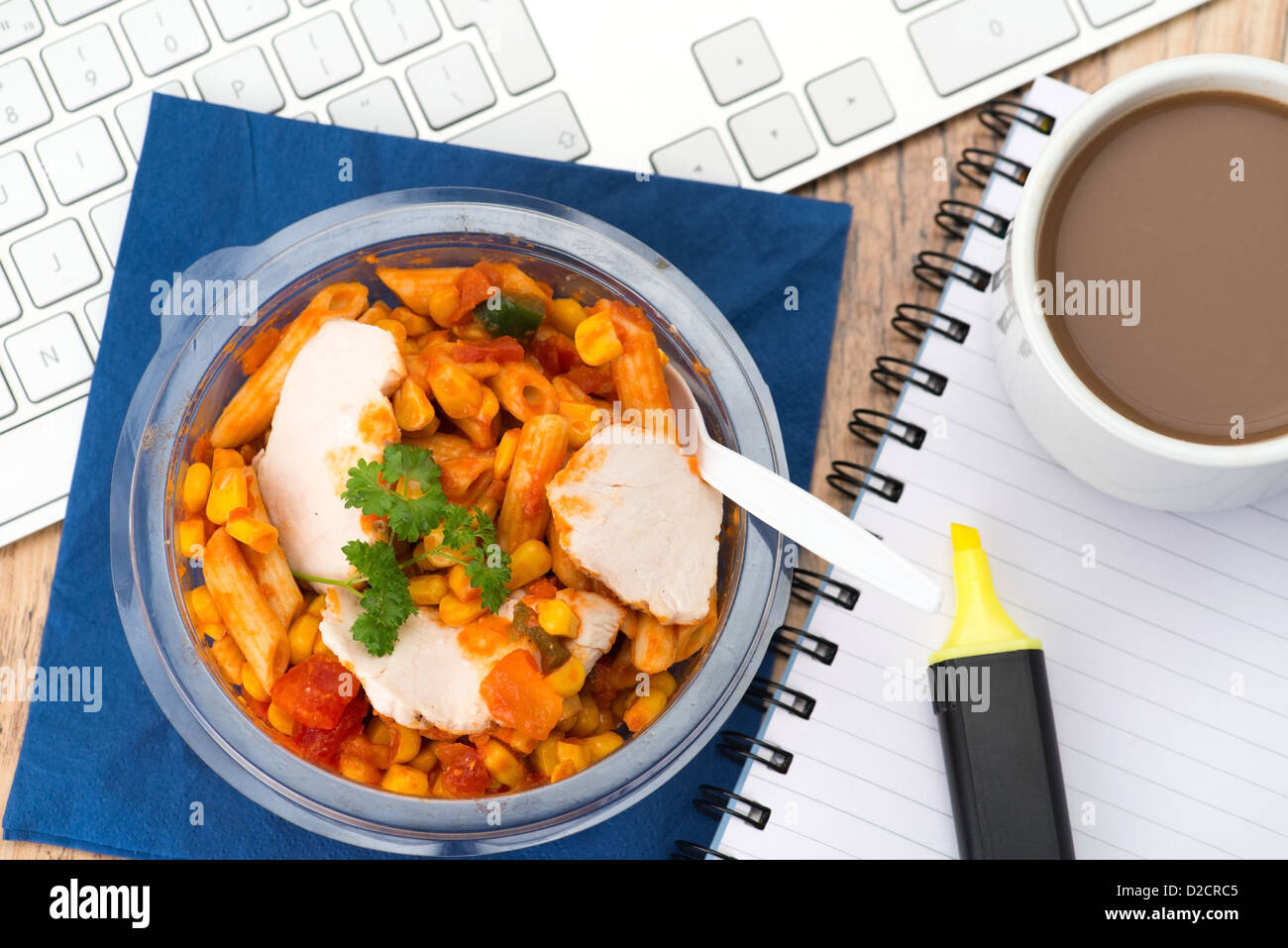 Pasta tubes in tomato sauce with chicken being eaten at an office desk. Stock Photo