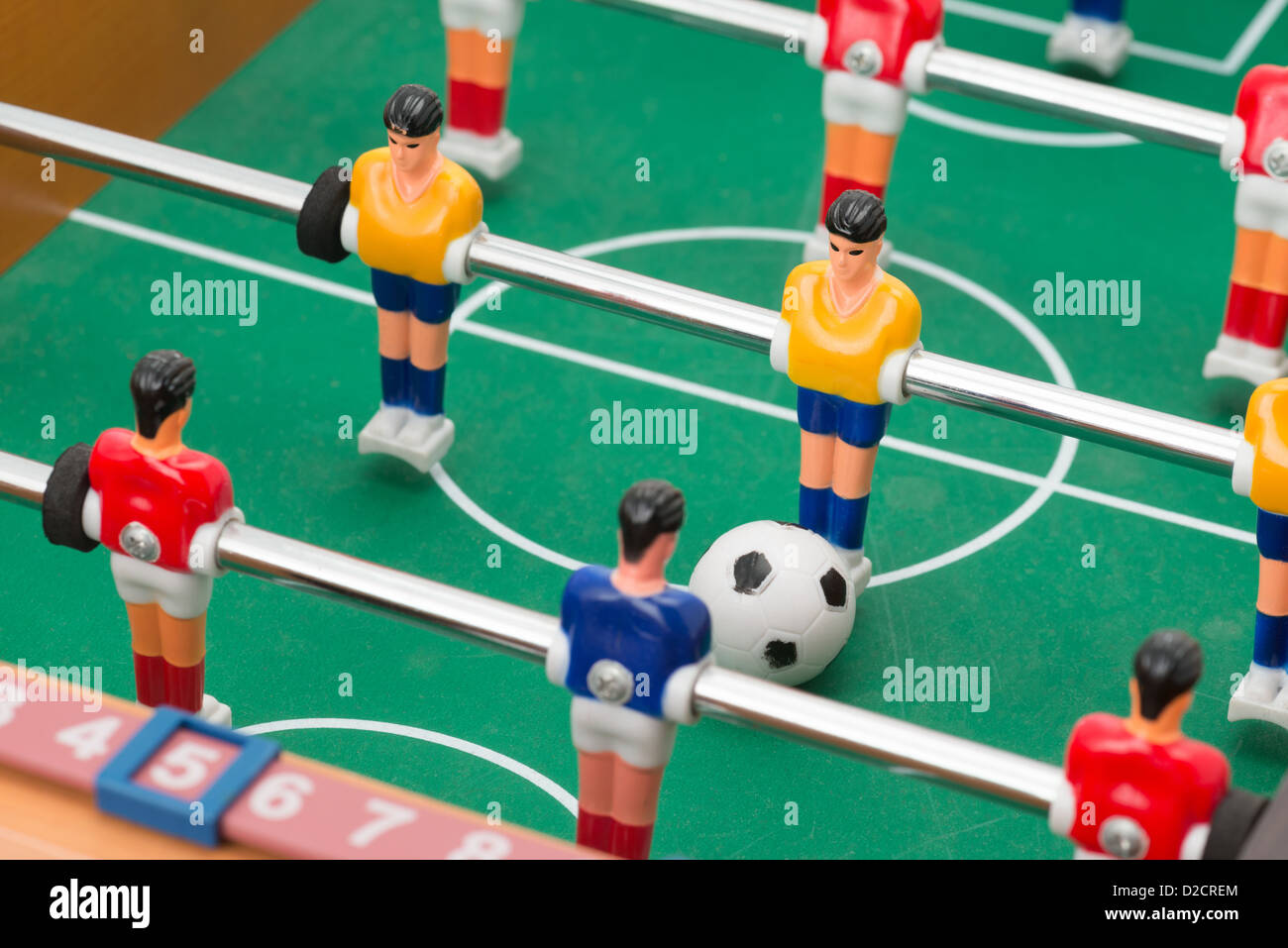 Close-up on the players of a table football game - Stock Image
