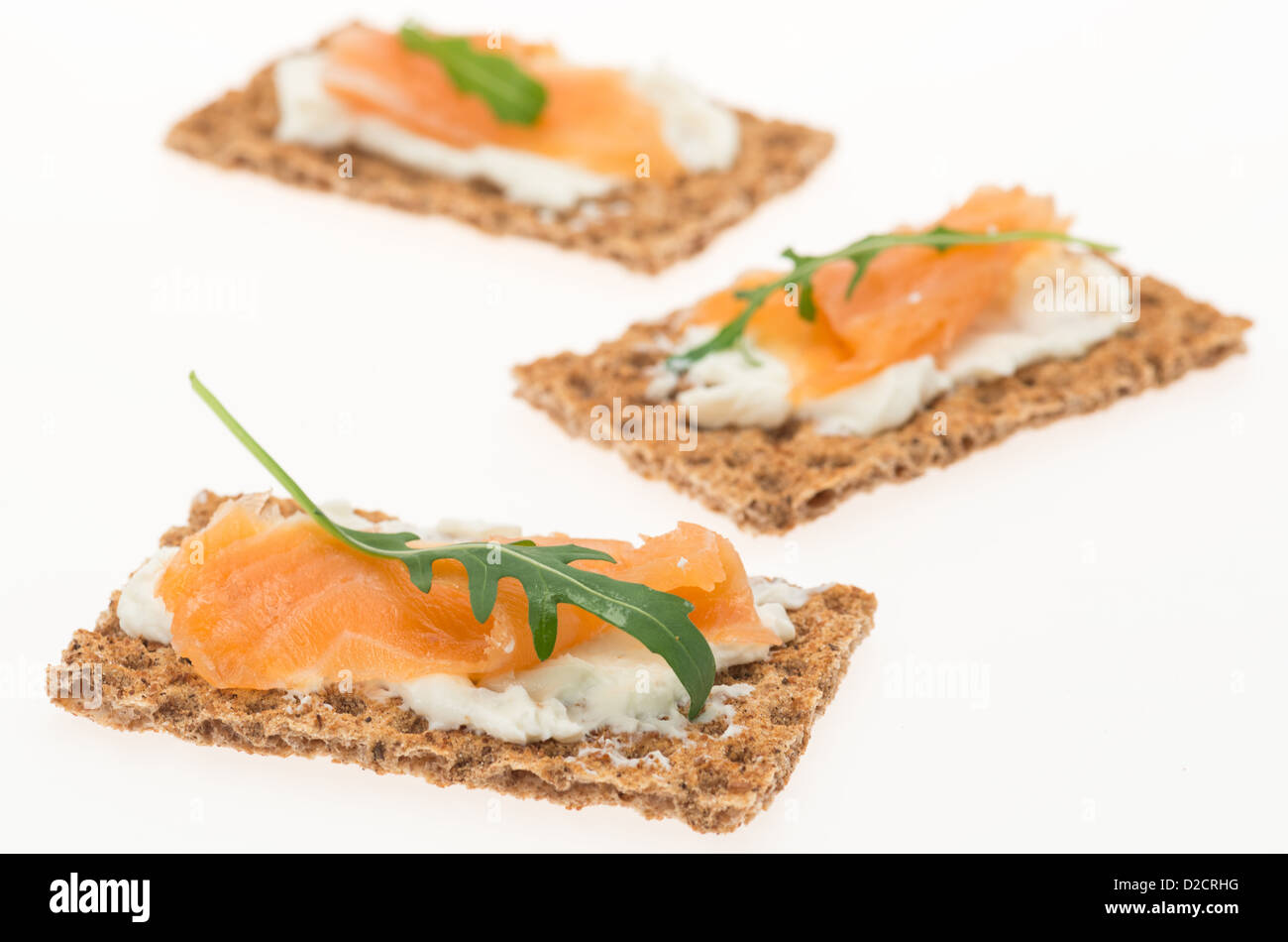 Crispbread with cream cheese and smoked salmon - studio shot with a white background and shallow depth of field - Stock Image