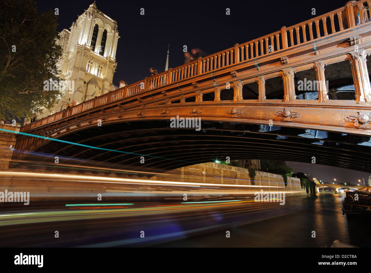 bridge 'pont au double' over the Seine and cathedral Notre Dame in Paris at night - Stock Image