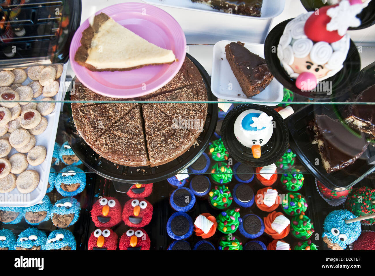 display of delicious baked treats pastries colorful novelty cookies including red Elmo & varieties in glass - Stock Image