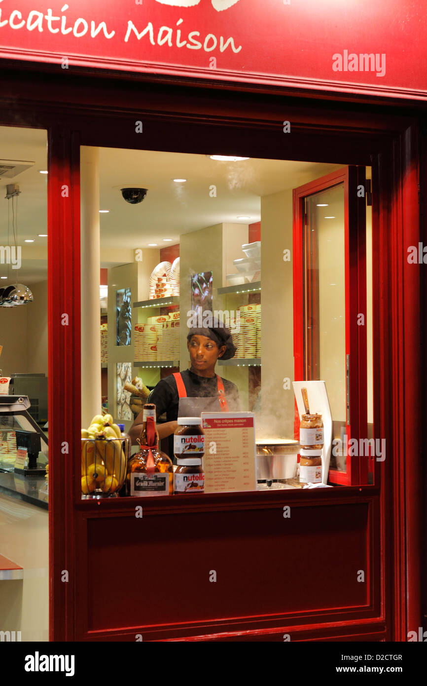 black saleswoman at the stand of a street sale in a cream shop in Montmartre - Stock Image