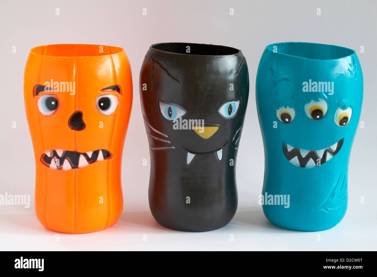 scary halloween faces on plastic beakers isolated on white background - Stock Image