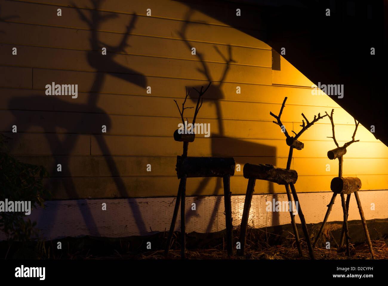 Christmas display of rustic reindeer and shadows. - Stock Image