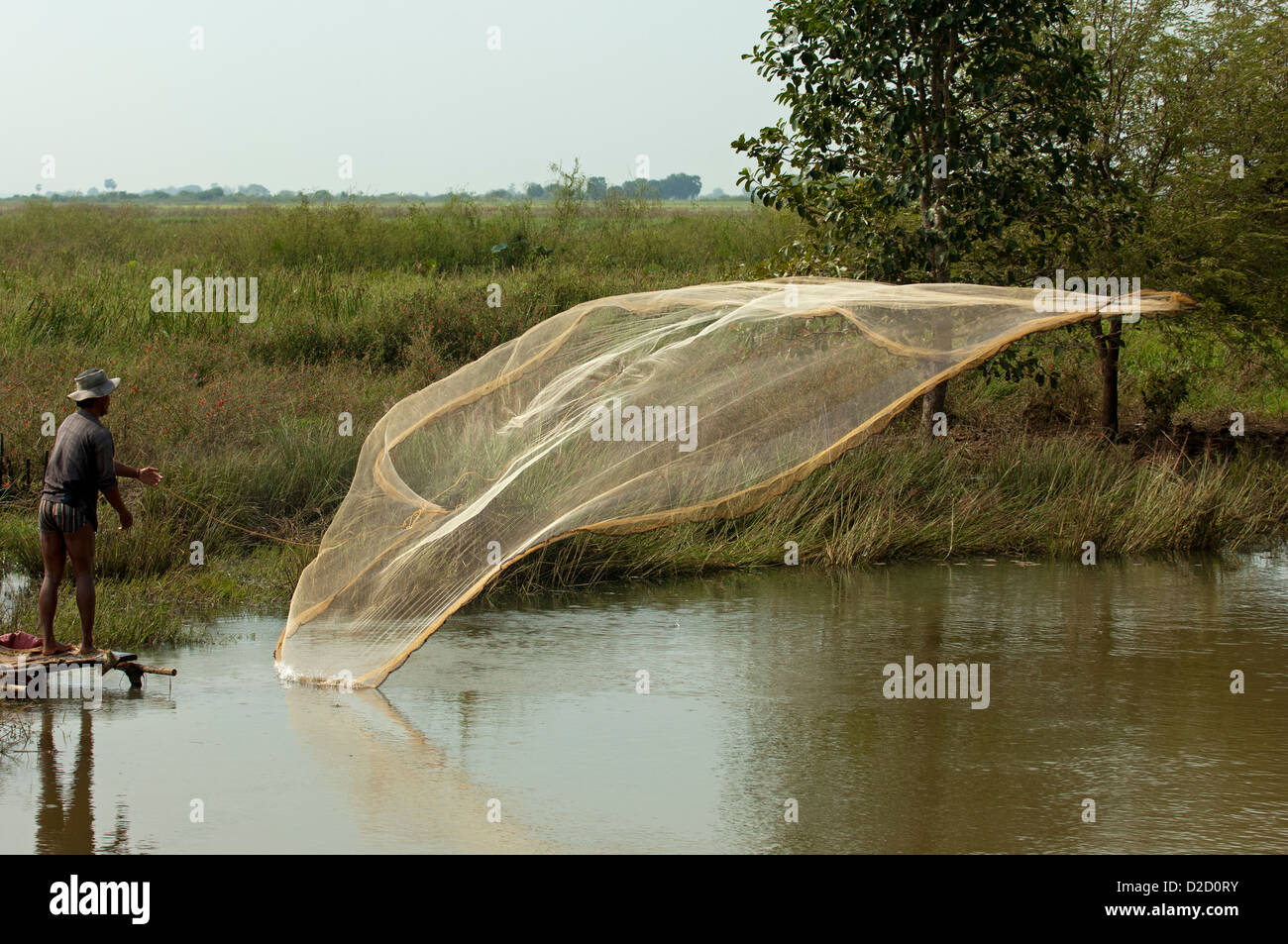Fisherman throwing a cast net in a river, Battambang, Cambodia - Stock Image