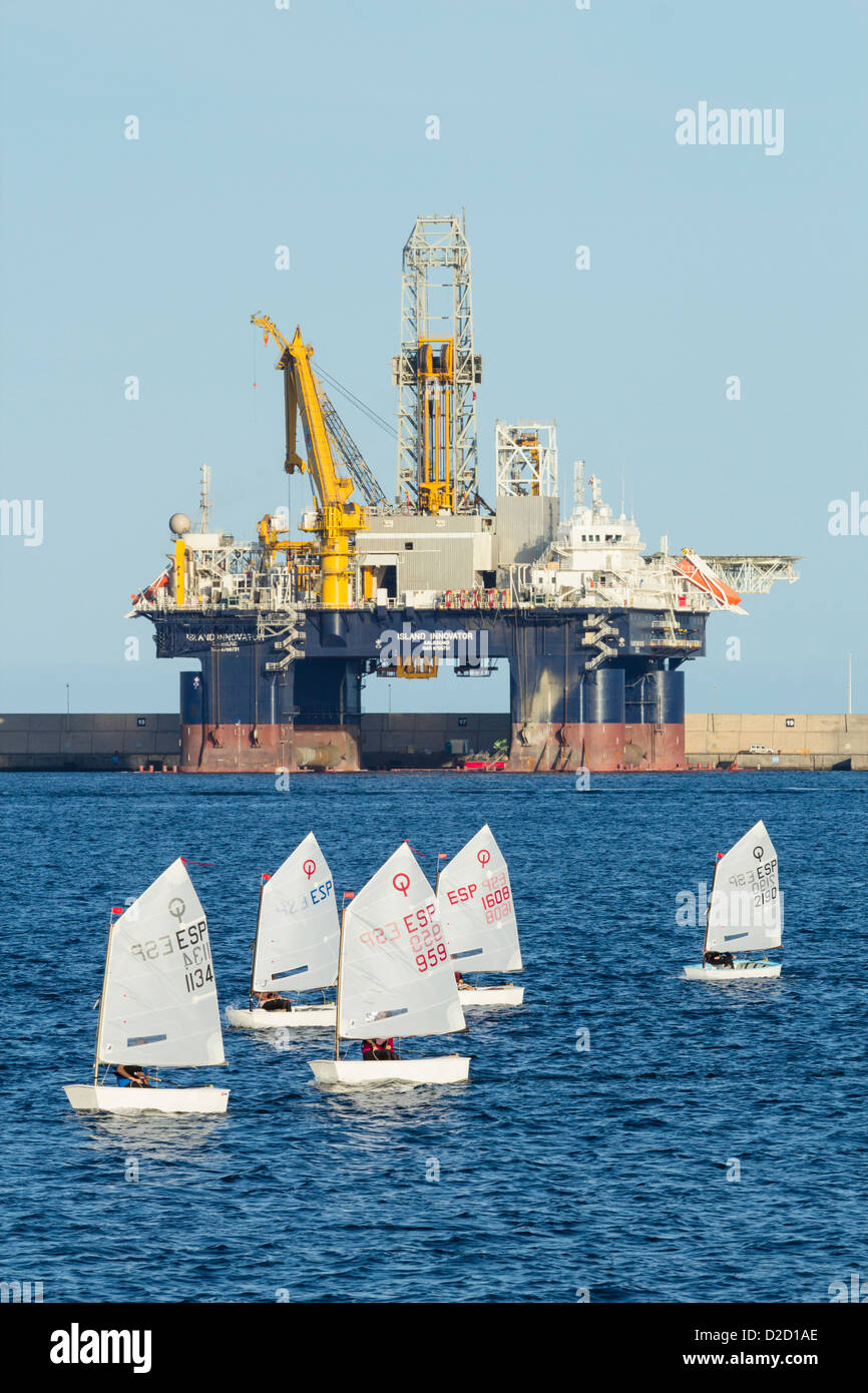 Optimist dinghies sailing in front of Island Innovator semi submersible drilling rig in Las Palmas port on Gran - Stock Image