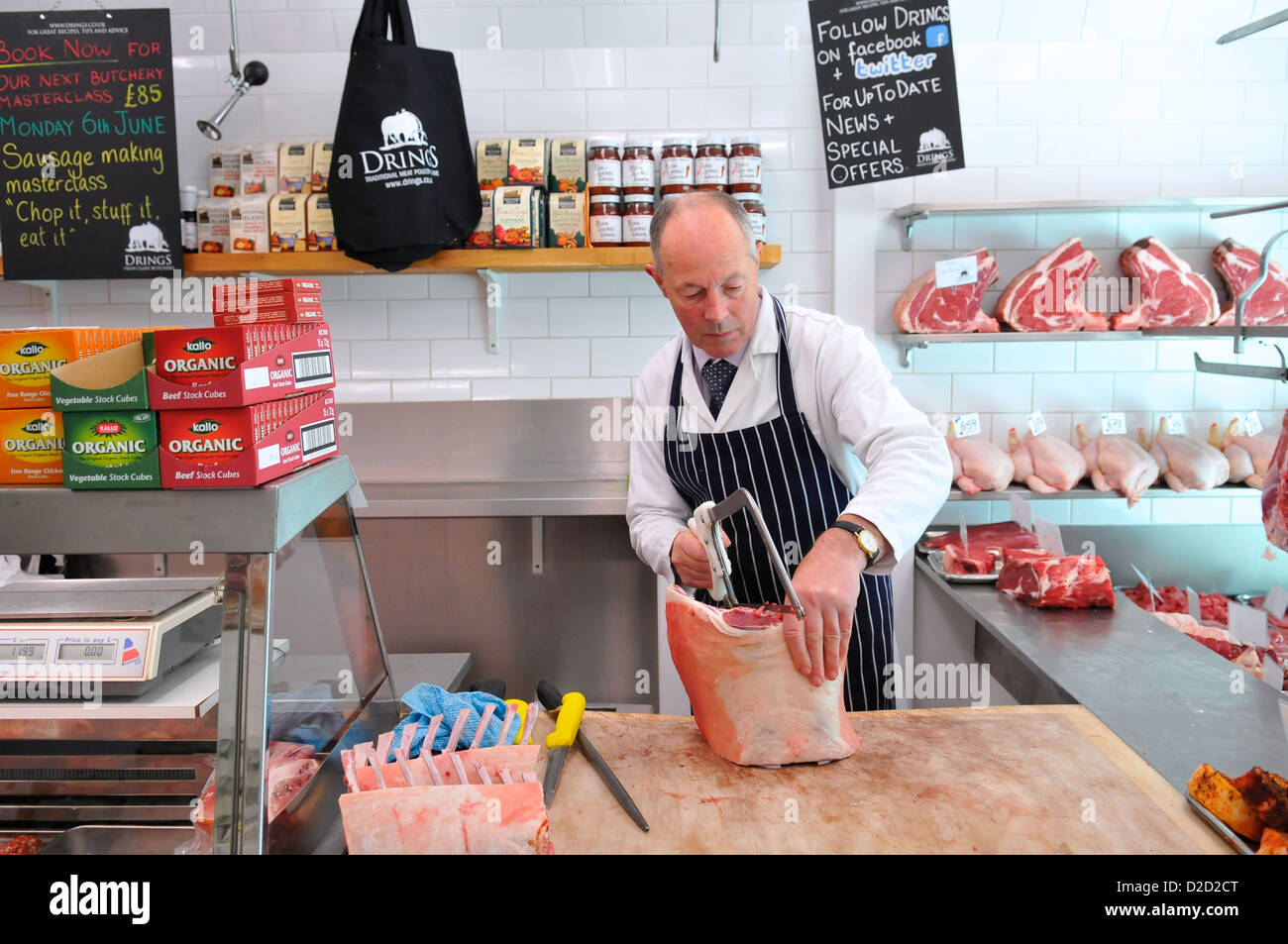 Butcher cutting meat at Drings Butchers, Royal Hill, Greenwich, South London, London, England, UK - Stock Image