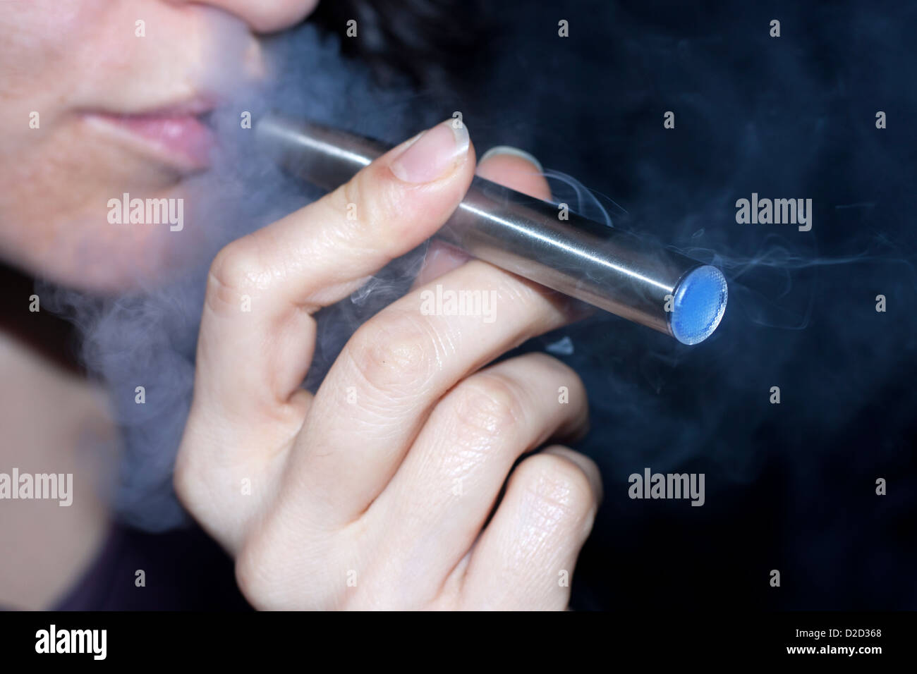 Woman smoking electronic cigarette closeup - Stock Image