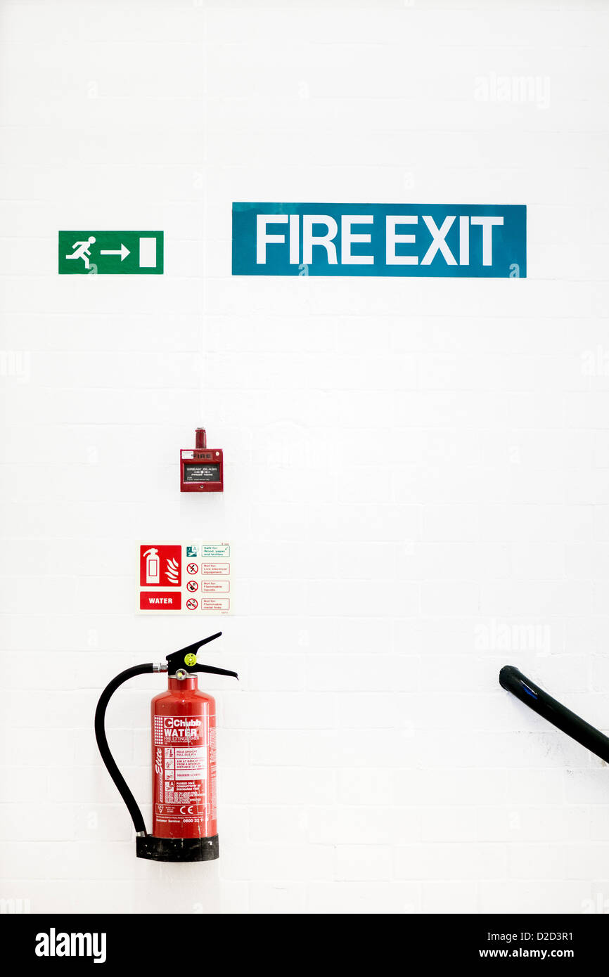 Fire safety Fire extinguisher fire alarm and fire exit signs on a wall - Stock Image
