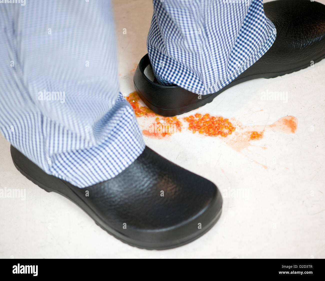 MODEL RELEASED Slip hazard Tomato seeds on a kitchen floor - Stock Image