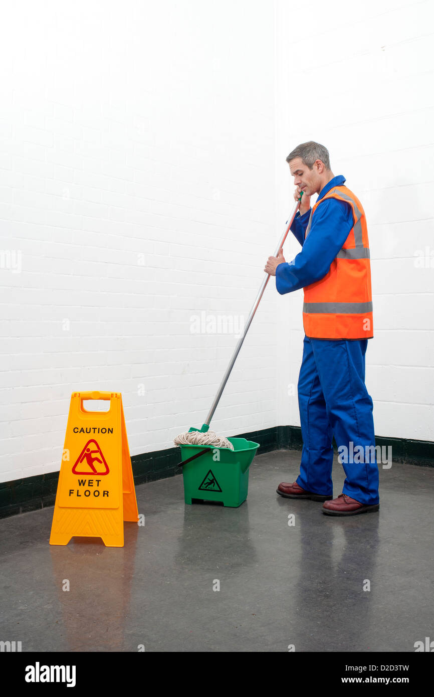 MODEL RELEASED Mopping floor Man mopping a floor next to a caution sign Stock Photo