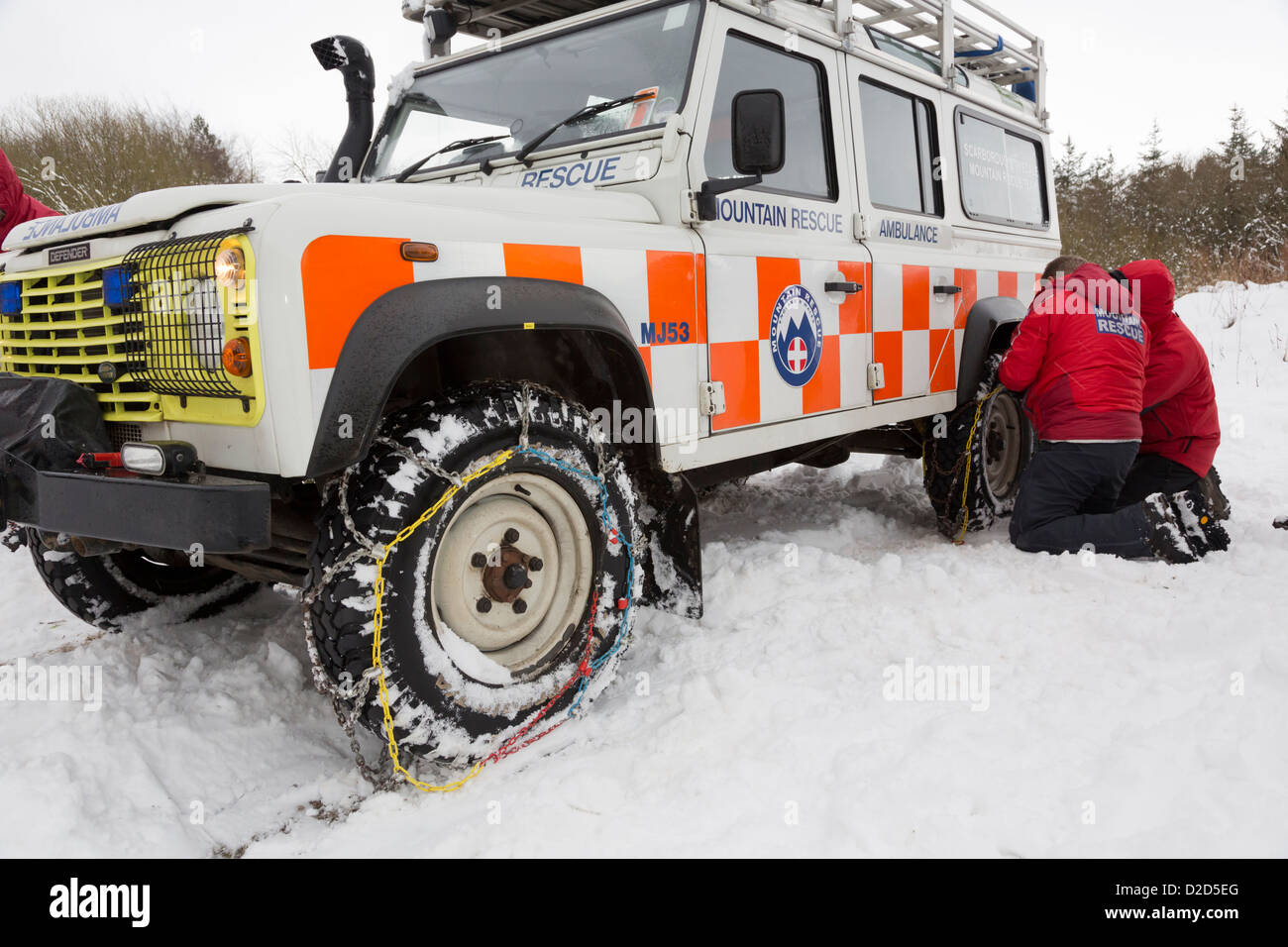 Scarborough & Ryedale Mountain Rescue team fitting snow chains, during a training exercise in Dalby Forest. - Stock Image
