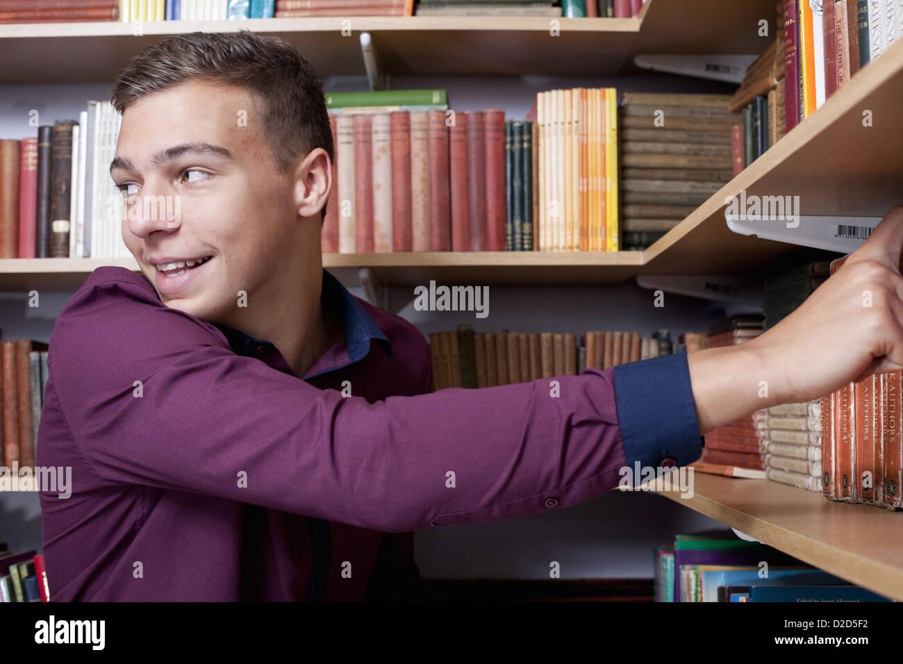 Student pulling books from bookshelf - Stock Image