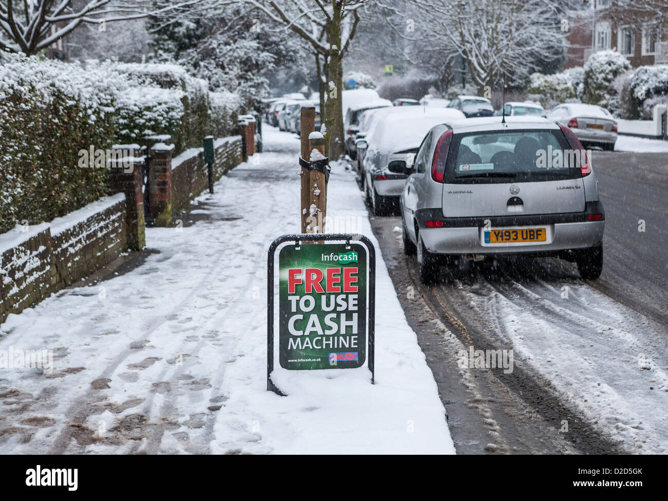 An advertisemnet for a 'free to use' cash machine in a snow covered suburban road - Strawberry Hill, Twickenham, - Stock Image