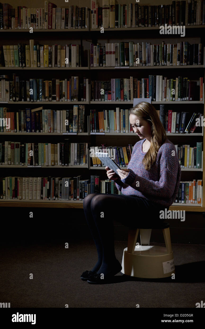 Student using tablet computer in library - Stock Image