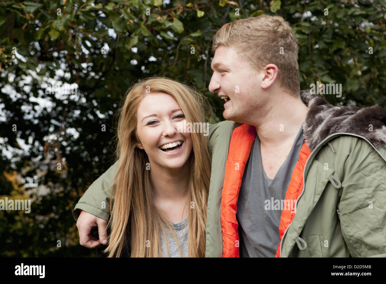Couple standing together in park - Stock Image