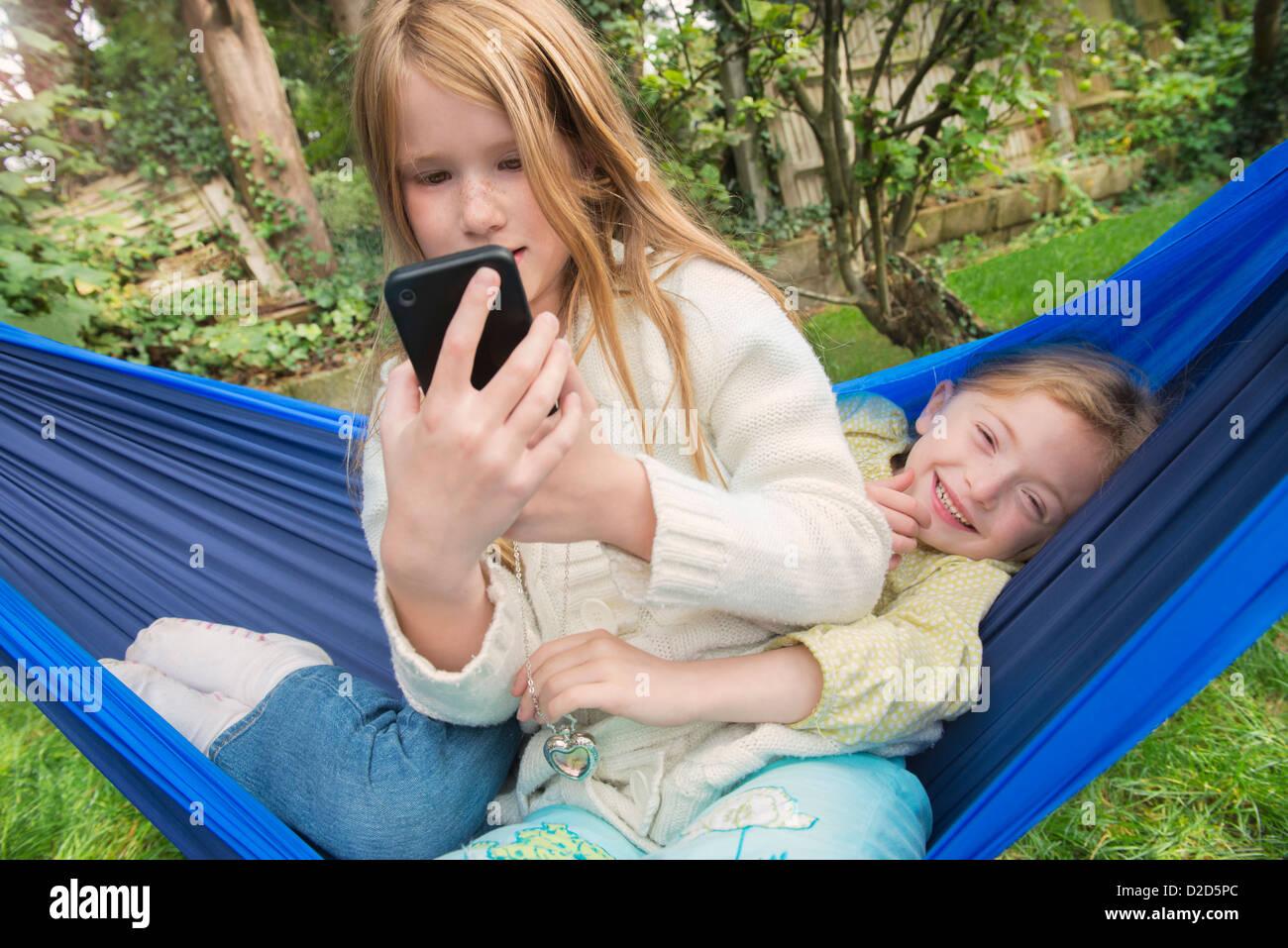 Children relaxing in hammock - Stock Image