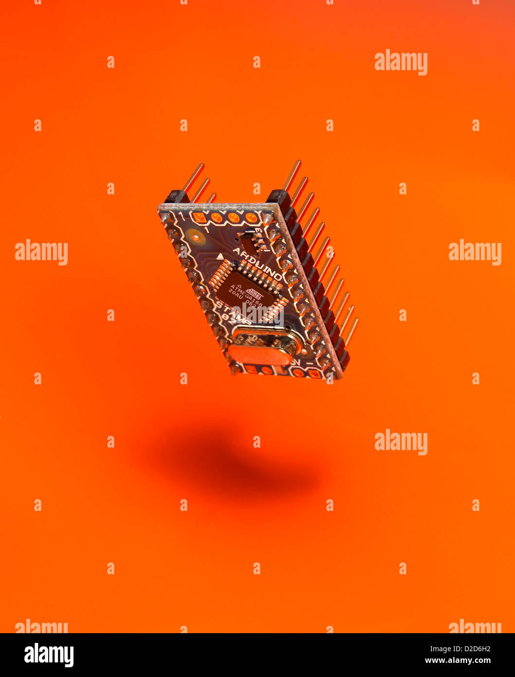 Micro chip suspended in air cut out orange background - Stock Image