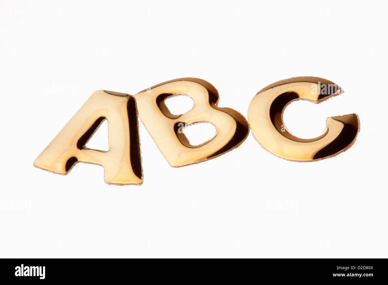The letters 'ABC' in gold lettering - Stock Image