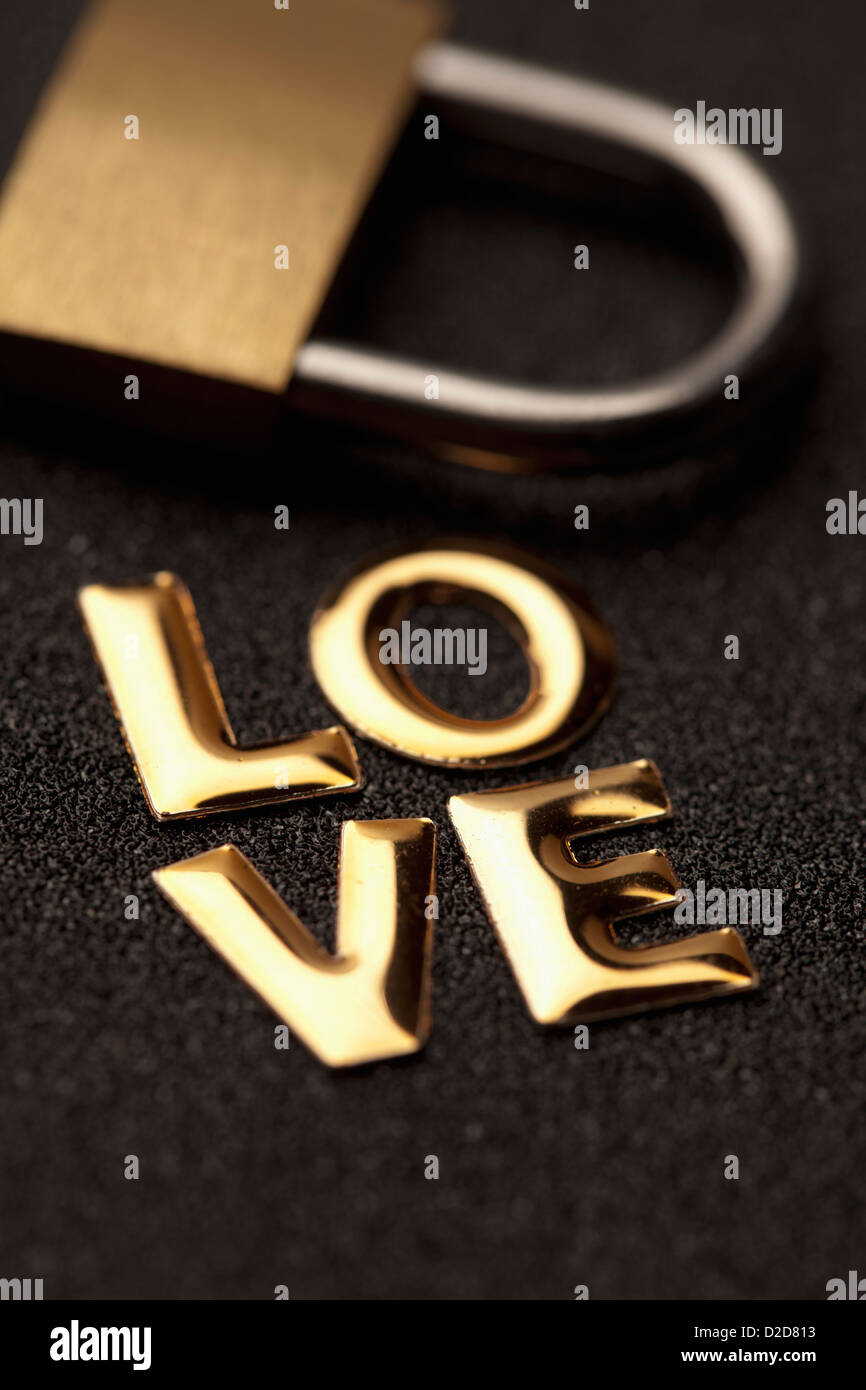 Single word 'love' in gold lettering beside padlock - Stock Image