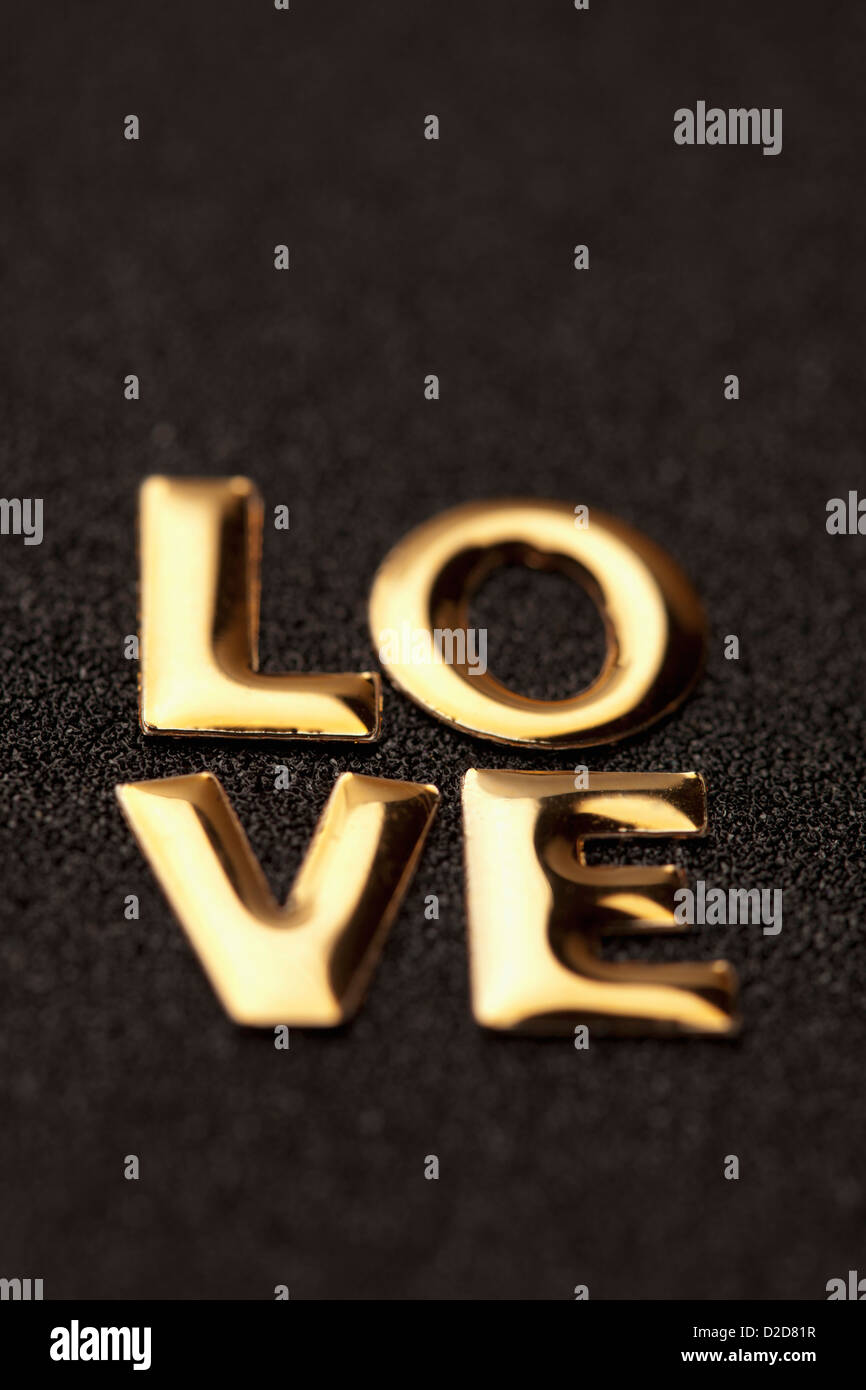 Single word 'love' in gold lettering - Stock Image