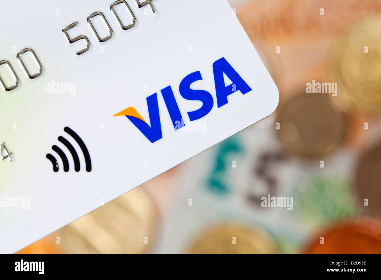 Bath, United Kingdom - November 8, 2011: Close-up of a contactless Visa credit card with UK currency in the background Stock Photo