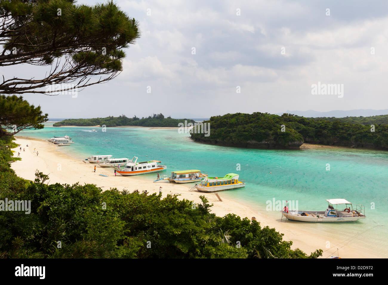 Kabira, Japan - April 6, 2012: Glass-bottomed tourist boats line the sandy beach at Kabira Bay, Ishigaki Island, - Stock Image