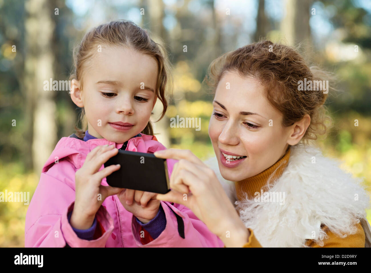 A young daughter showing her Mom something on a smart phone - Stock Image