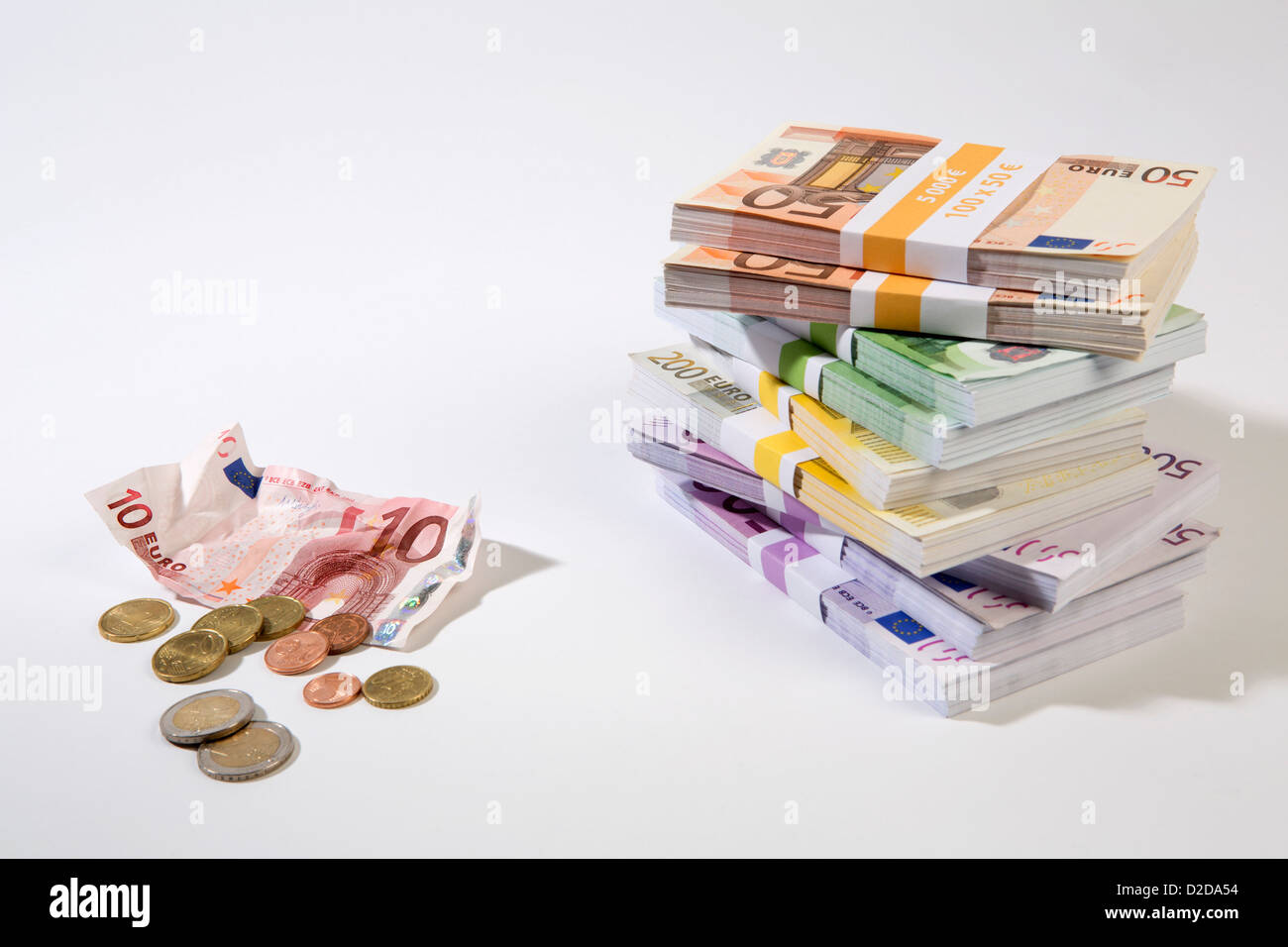 Stack of large billed Euro banknotes next to a crumpled ten note and change - Stock Image