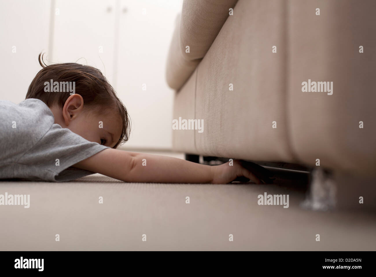 A boy reaching under a sofa to retrieve something - Stock Image