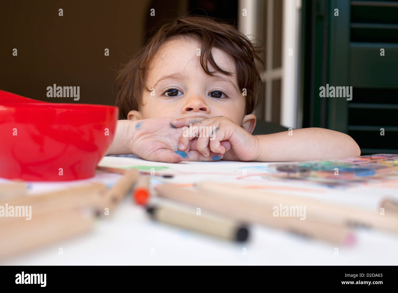 A child leaning on a table littered with colored pencils and art supplies - Stock Image