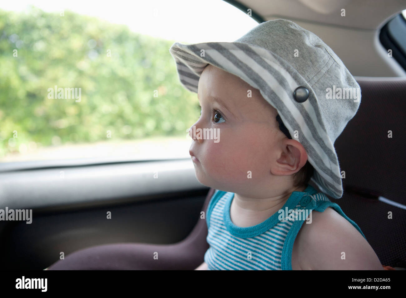 A child anticipating a car ride, sitting in car seat - Stock Image