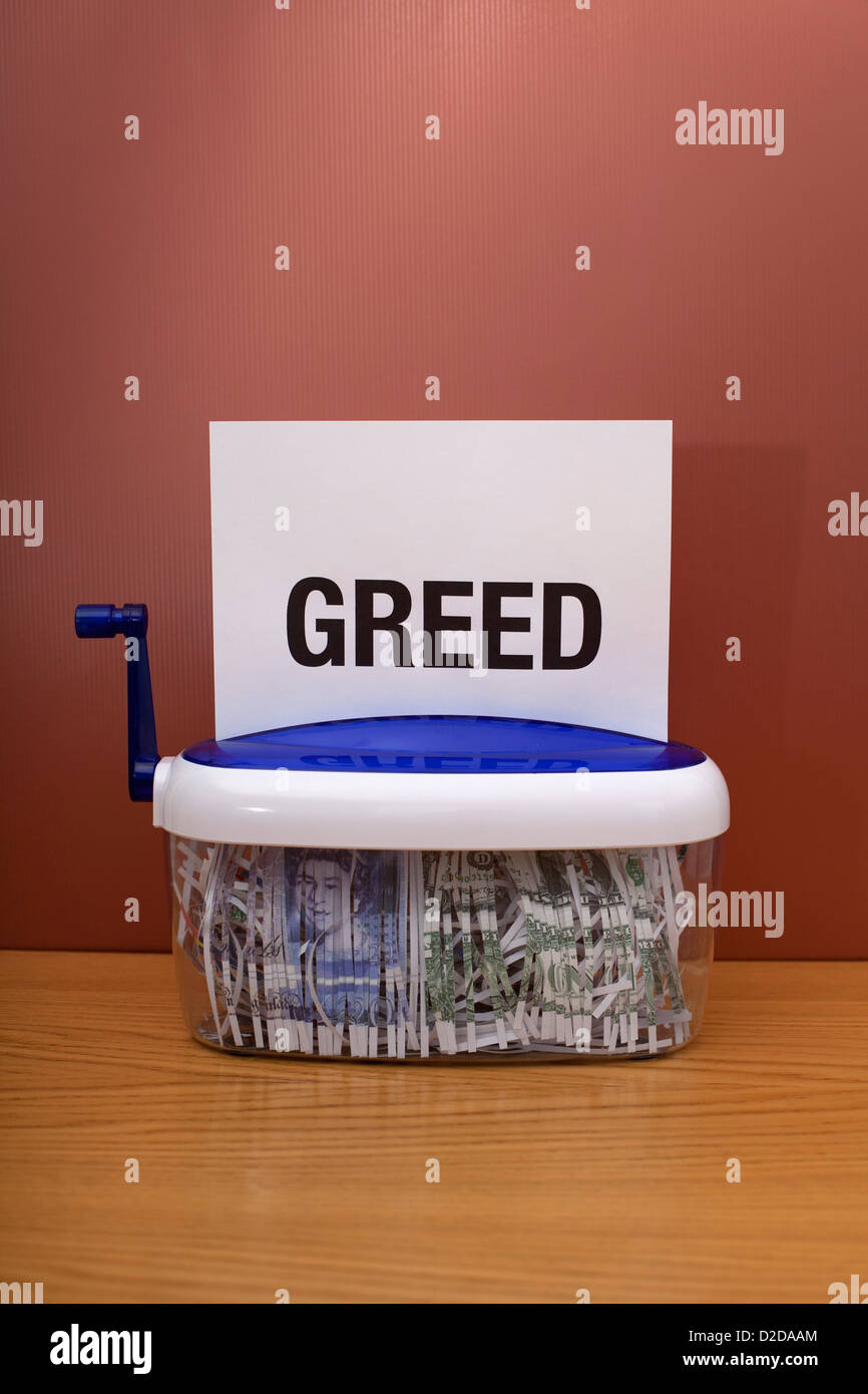 Money being shredded with the word 'greed' on top of the page - Stock Image