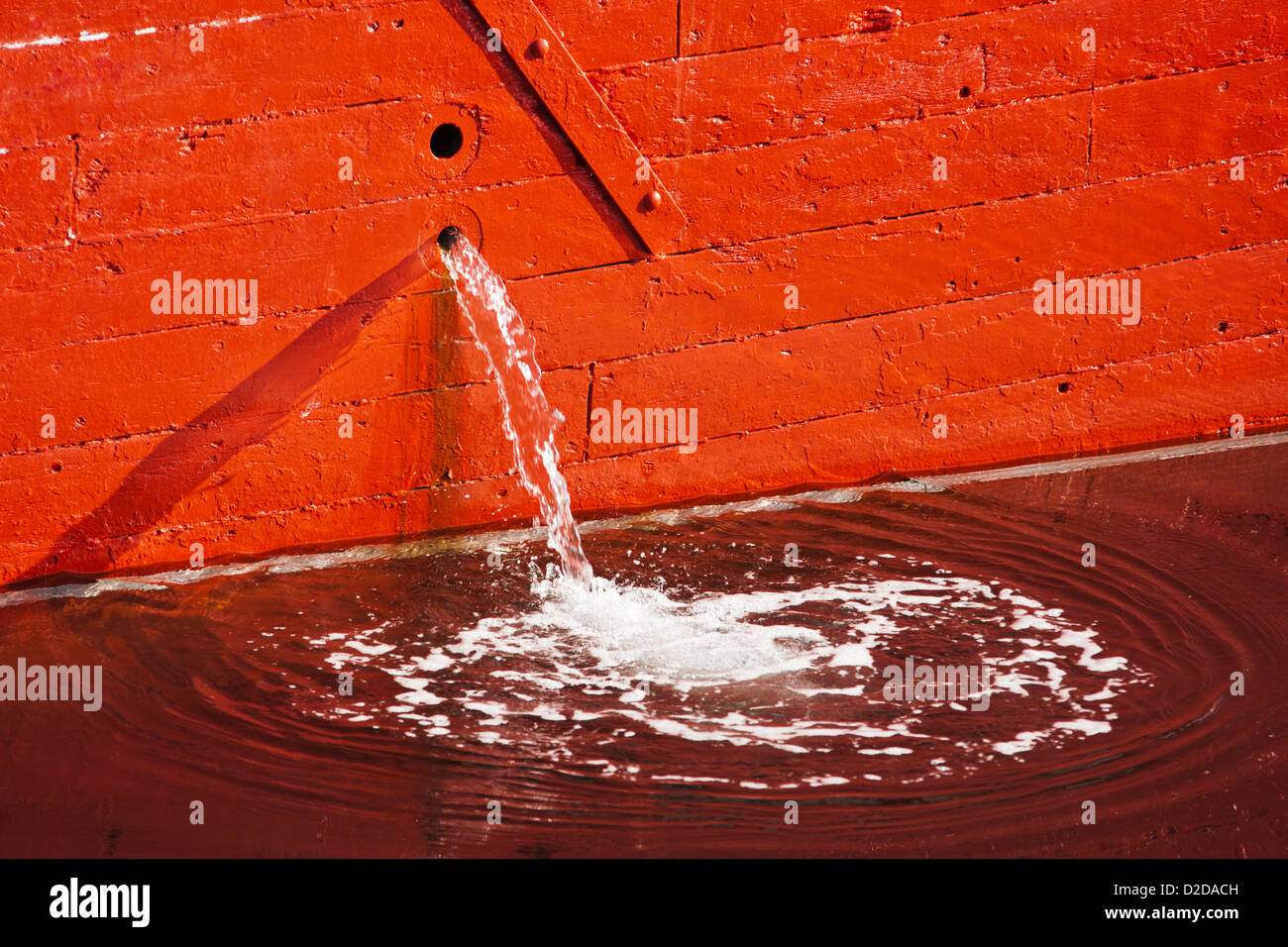 A bilge pump ejects water from the side of a fishing boat. - Stock Image