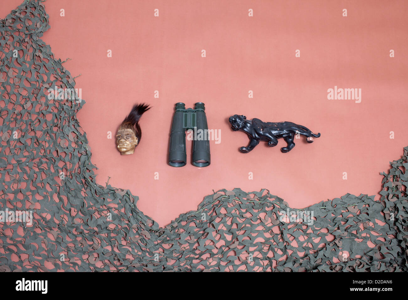 A shrunken head, binoculars, a jaguar and camouflage netting - Stock Image