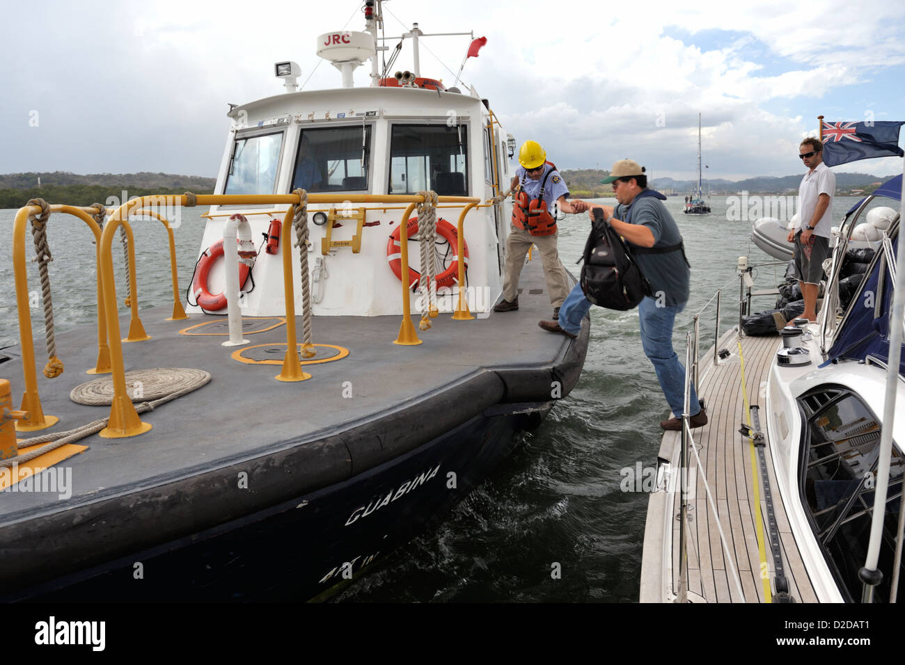 A Panama Canal advisor jumping onto an ACP pilot boat alongside a cruising yacht at the Pacific end of the Panama - Stock Image